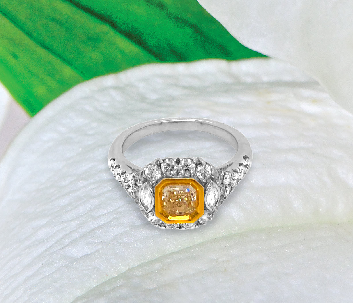 18K white gold diamond engagement ring featuring a 0.74 carat natural fancy yellow diamond bezel set in yellow gold, and marquis round diamonds weighing a total of 0.99 carats. Total diamond weight: 1.73ctw.