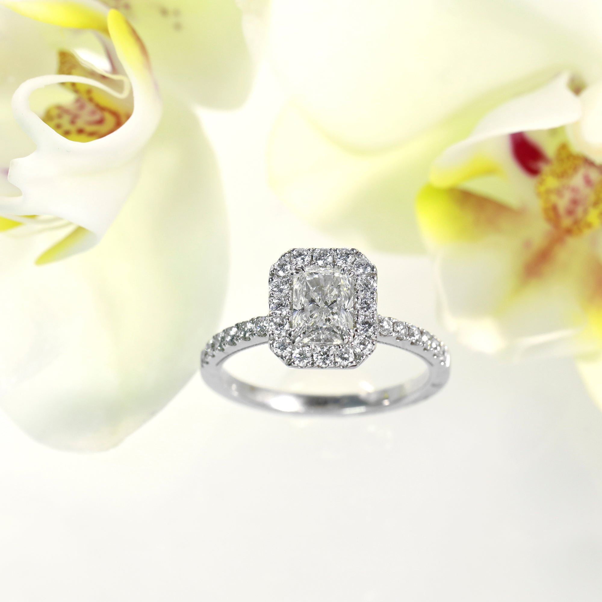 14K white gold diamond engagement ring featuring one rectangular radiant diamond, and a diamond halo and side stones with round brilliant diamonds.