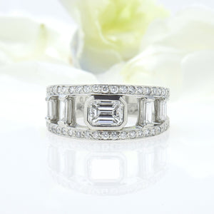 Kwiat platinum diamond band set with one emerald-cut diamond, 4 baguette diamonds, and 42 round diamonds.