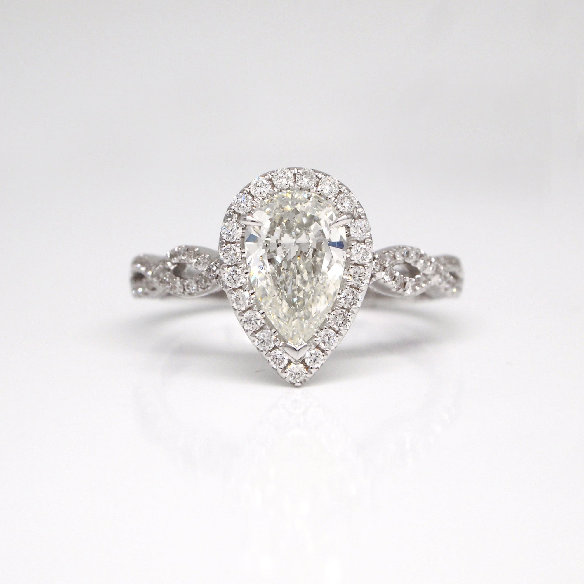 1.00 carat pear-shaped diamond set in 14K white gold with 79 brilliant cut diamonds weighing a total of 0.31 carats