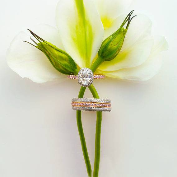 18K rose and white diamond engagement ring featuring 1 oval diamond set in a white gold diamond halo, and round pink diamonds in rose gold in a full eternity design. Matching 18K wedding band features white and pink diamonds set in a full eternity design.
