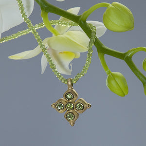Yellow gold pendant set with 5 round peridots on a peridot briolette necklace