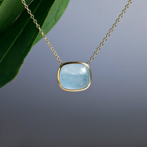 14K yellow gold aquamarine necklace featuring 1 cabochon-cut blue aquamarine weighing 12.33 carats in a bezel setting.