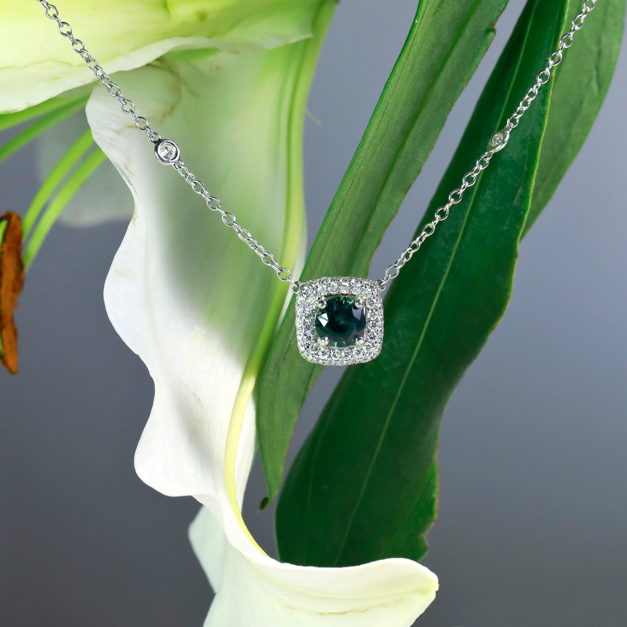 18-inch 18K white gold blue-green sapphire and diamond necklace featuring one round 1.63 carat blue-green sapphire, and round brilliant diamonds set in a cushion shaped halo and 8 bezel-set diamonds set along the chain.