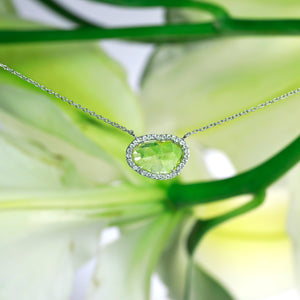 14K white gold diamond necklace featuring one lightly faceted diamond slice weighing 0.60 carats, and a diamonds halo with round brilliant diamonds weighing a total of 0.16 carats.