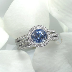 14K white gold sapphire engagement ring featuring 1 round ceylon blue sapphire bezel set in diamond halo in a full diamond eternity design. Available with a matching diamond eternity wedding band (ring guards). Judith Arnell Jewelers