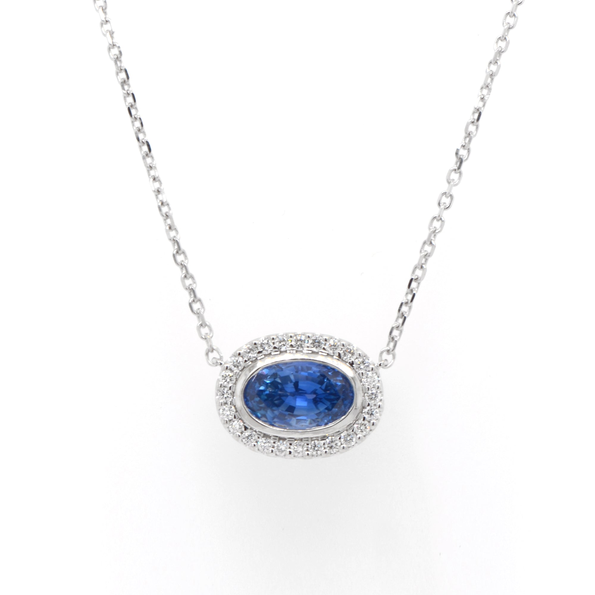 14K white gold sapphire and diamond necklace featuring one 2.90 carat oval blue sapphire set East-West in a diamond halo (0.24ctw).