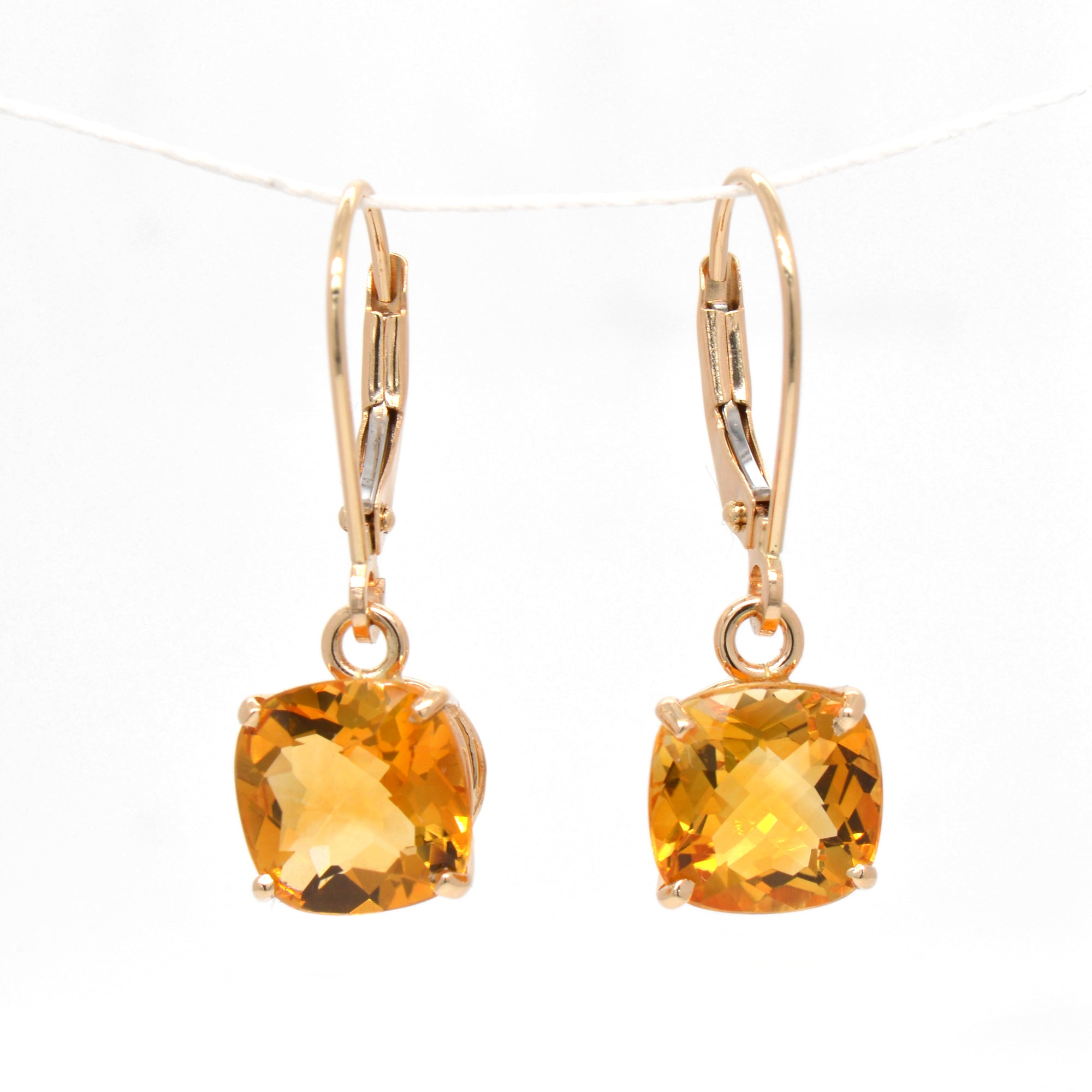 14K yellow gold citrine earrings featuring 2 golden yellow-orange cushion-shaped citrines measuring 8x8 mm.