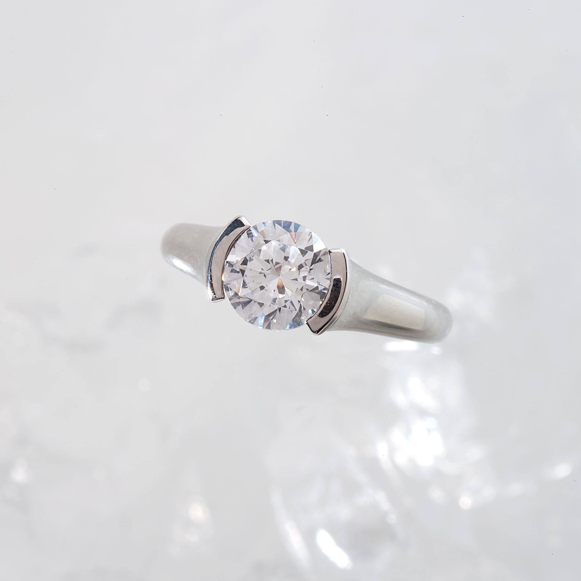 Diamond engagement ring featuring a round brilliant-cut diamond. and channel-set princess-cut diamonds. Custom-made to order for any size diamond or gemstone center stone. Available in 14K or 18K white, yellow, rose gold, and platinum.