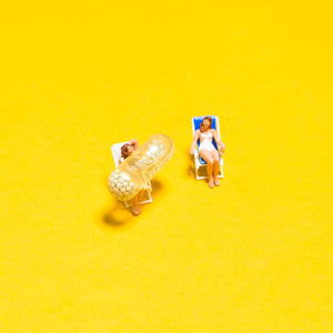 Tiny dolls on beach chairs, with Ritual's vitamin (Essential for Women) on a bright yellow background.