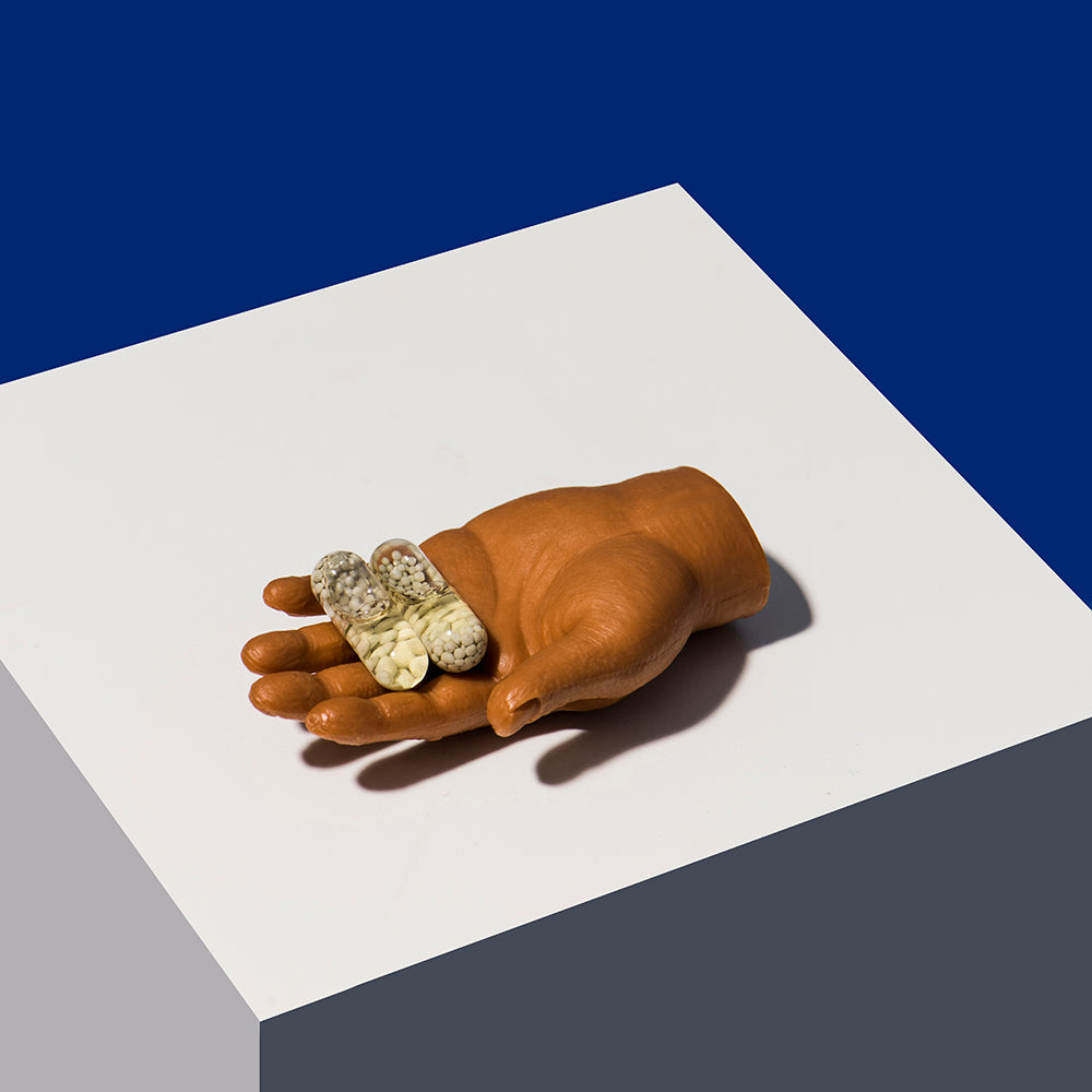 Doll hand holding two of Ritual's Essential for Women multivitamin pills on a white block against a navy blue background.