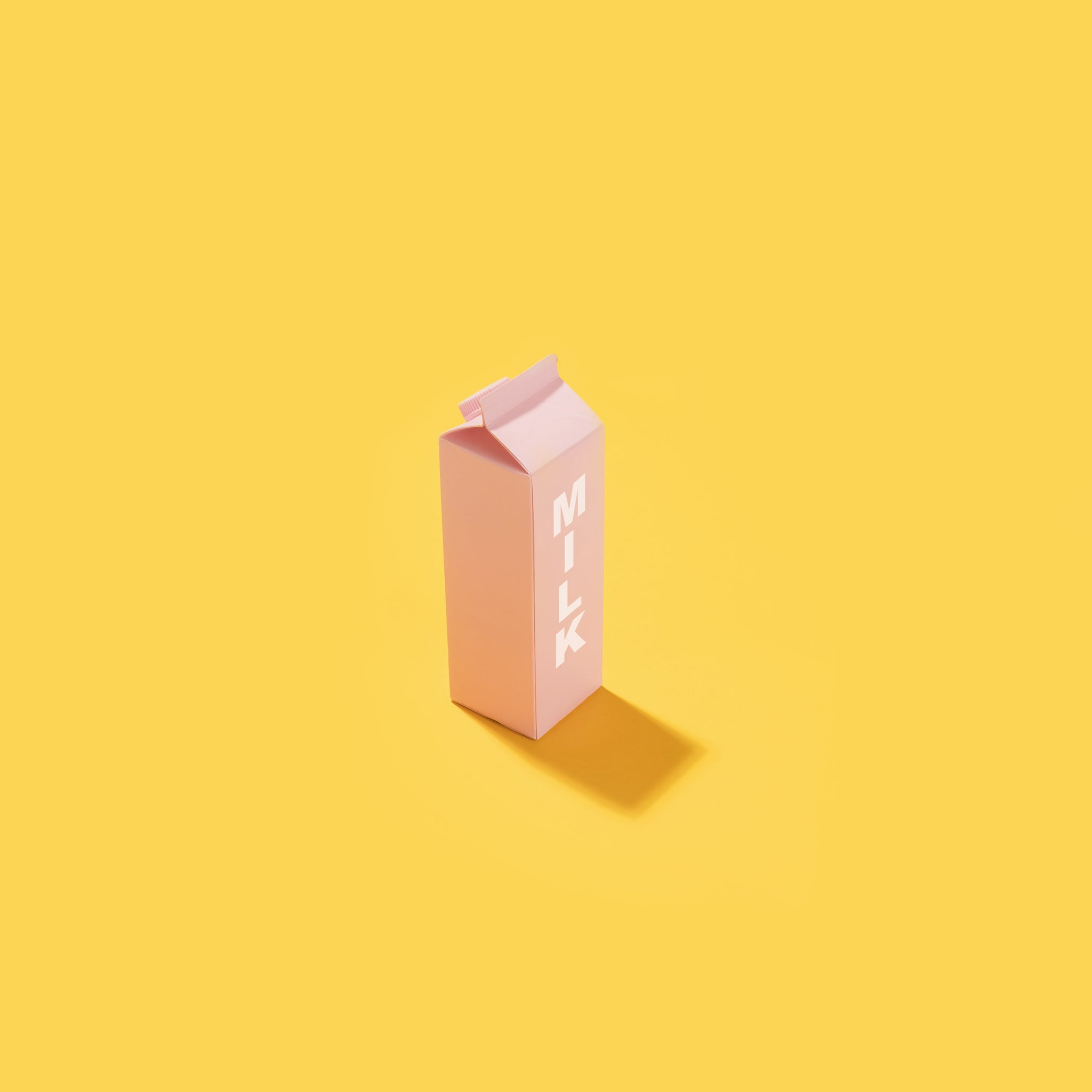 Pastel pink milk carton on a yellow background