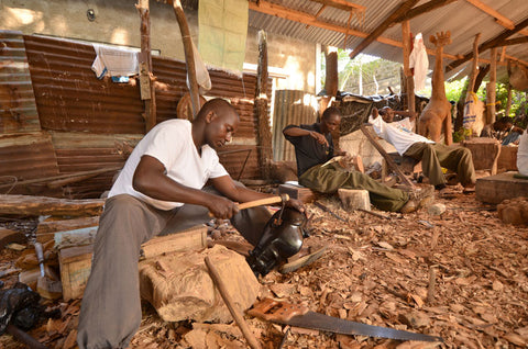 African wood sculptors sitting in piles of wood chips and crafting
