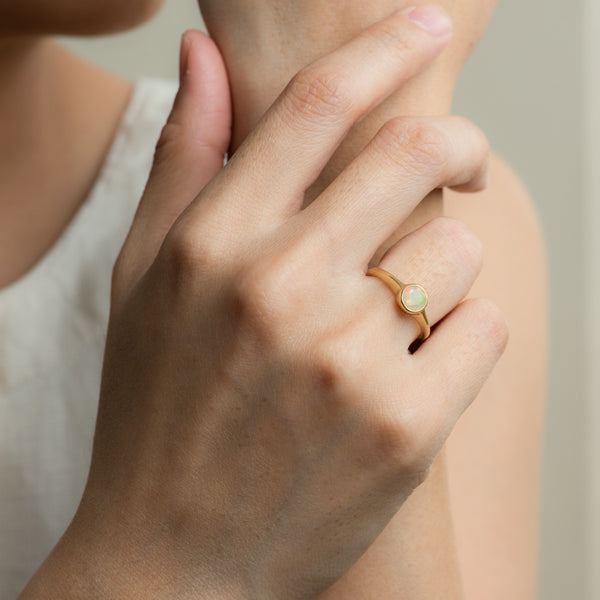 Opal on gold ring Ohana worn on hand model