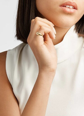 Woman holding hand in front of neck with pinky ring