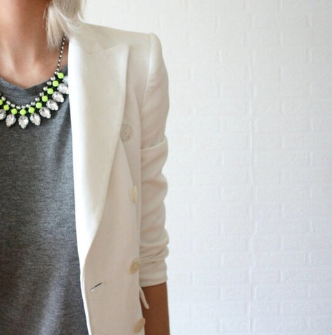 Woman wearing white blazer and geometric necklace