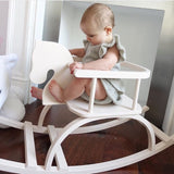 baby in a white wooden petit puk rocking horse
