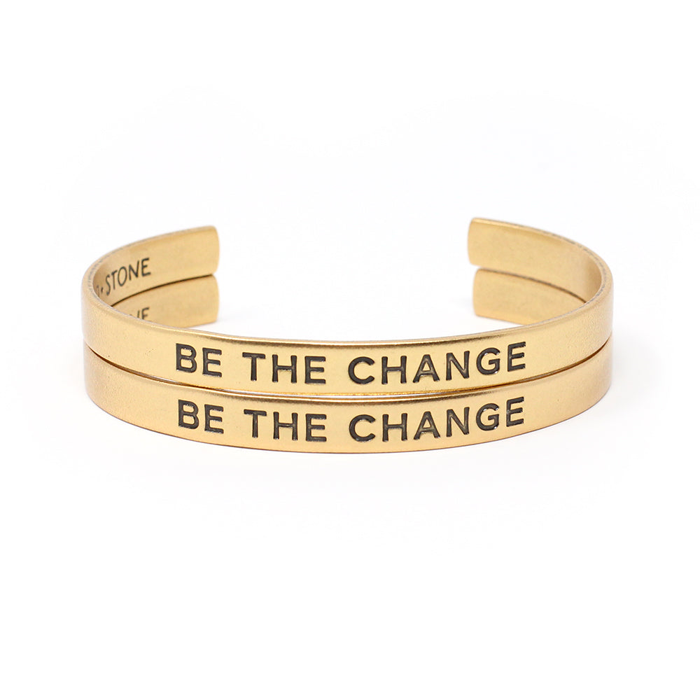 Set of two bracelets (two gold cuffs) that say 'Be the Change'