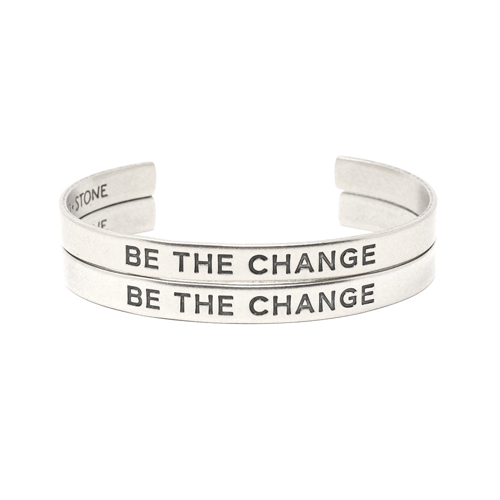 Set of two bracelets (two silver cuffs) that say 'Be the Change'
