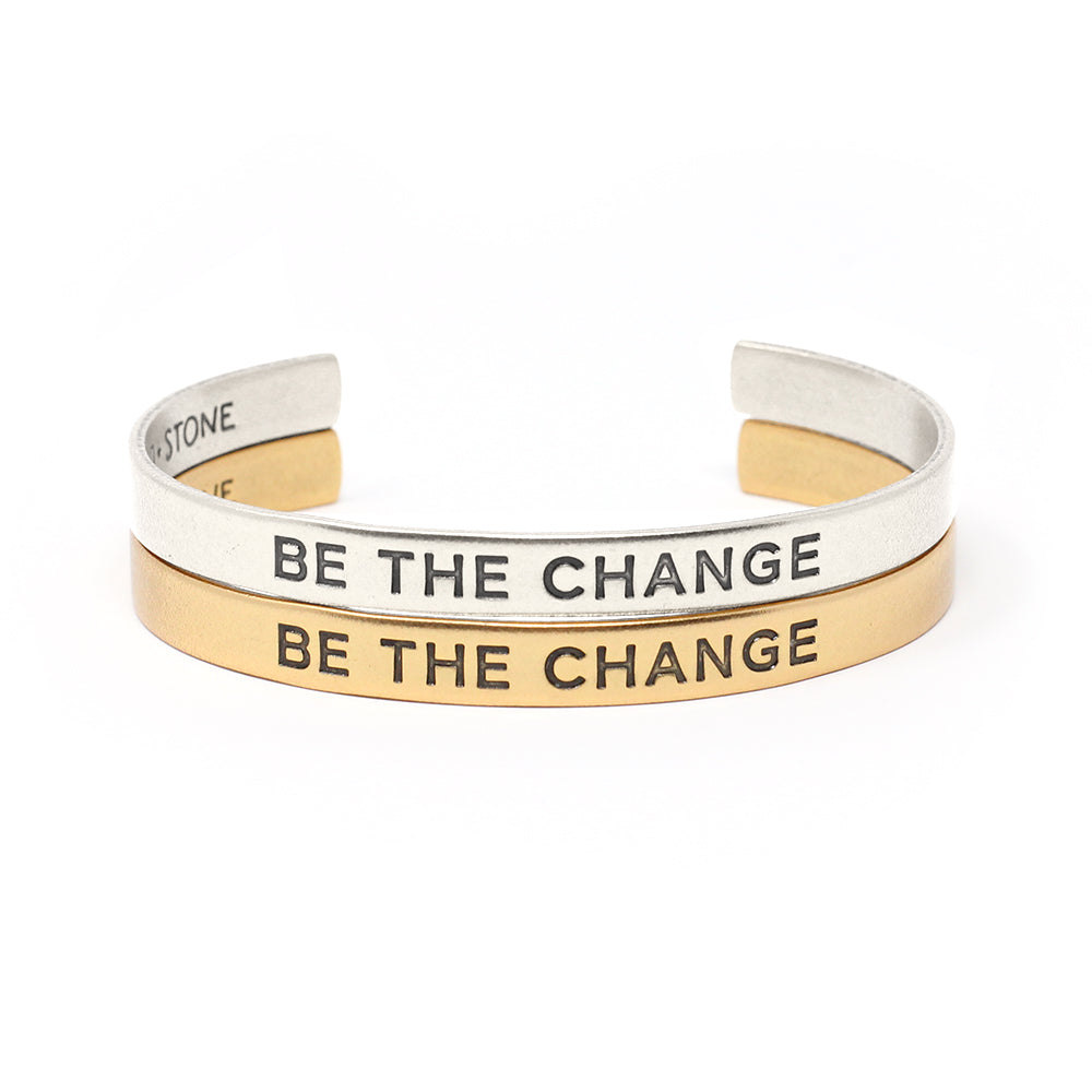 Set of two bracelets (one gold cuff and one silver cuff) that say 'Be the Change'