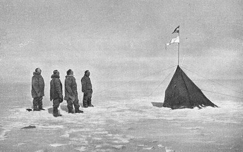 Amundsen and his crew look at the Norwegian flag on the South Pole in 1911