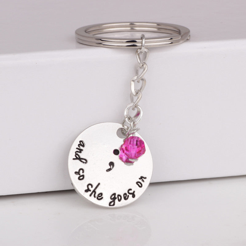 """and so she goes on"" semicolon keychain"