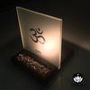 Frosted Glass Tealight Candle Holder with Om Symbol lit up at night with a burning candle