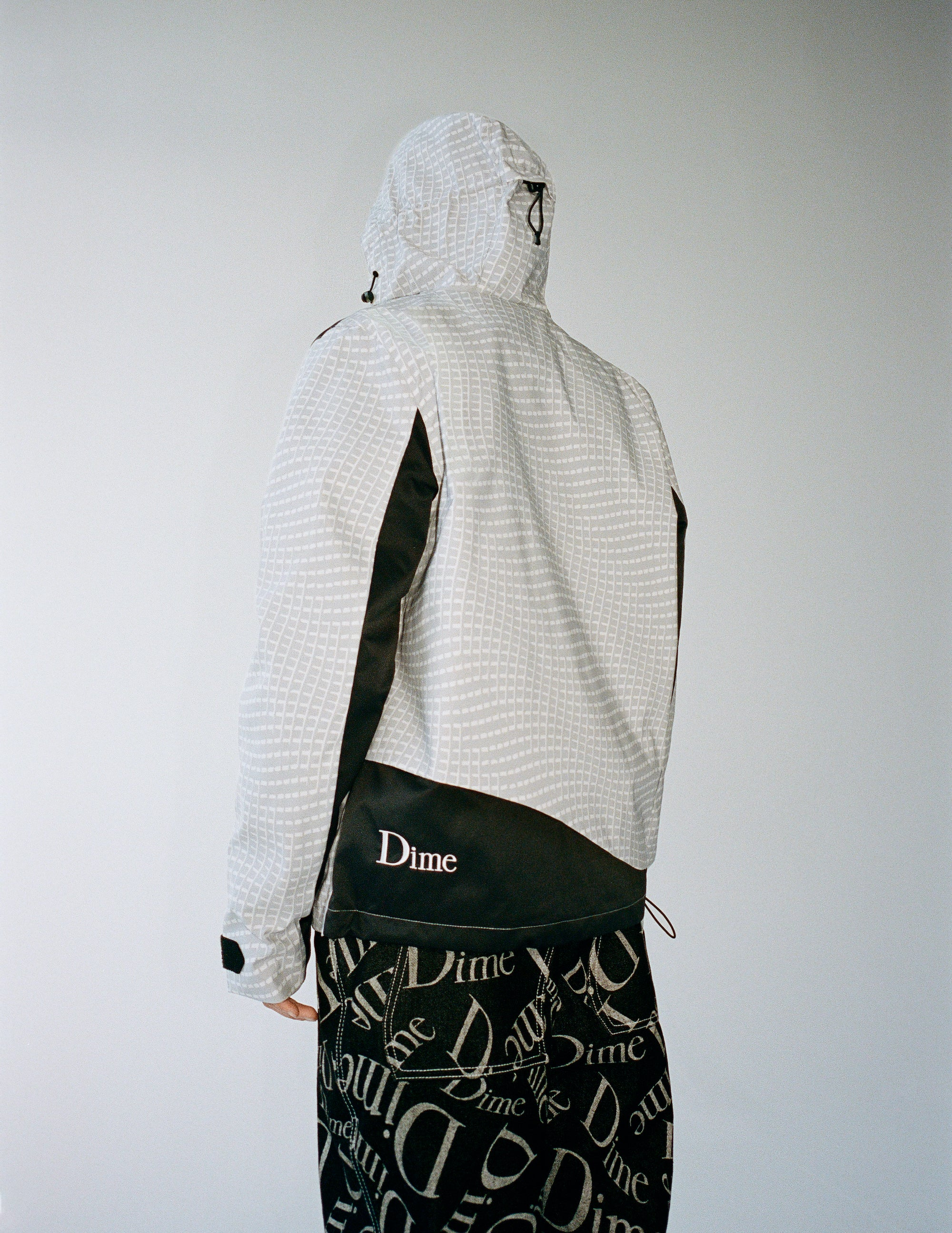 Dime Spring 2021 Lookbook Warp Shell Windbreaker in Gray styled with Online Exlusive Cotton Denim Pants in Black All Over Logo Print
