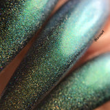 Close up of Aamon nail polish on stiletto nails, a green/blue multichrome holo polish