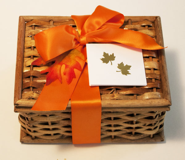 Image of a cute basket hamper wrapped in an orange satin bow containing pumpkin bread decorated with edible autumn leaves as a Thanksgiving mail delivery gift from Benedict Treats