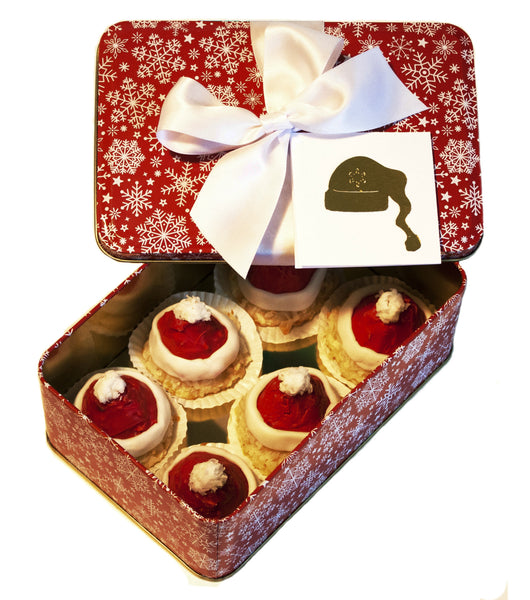 Image of coconut macaroons decorated to look like a Santa Hats in a festive holiday gift tin from Benedict Treats
