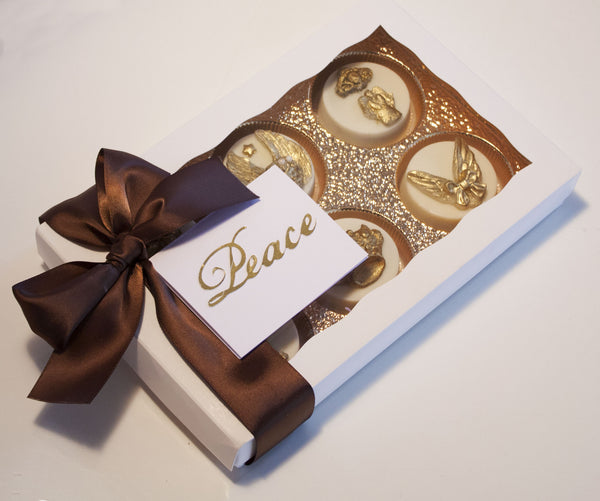 Image of a satin bow wrapped white gift box containing white chocolate covered oreos® with an ornate edible gold angel design on top as a cookie delivery gift from Benedict Treats