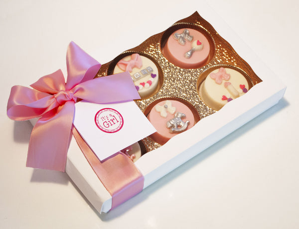 Image of pretty white box wrapped with a pink bow containing chocolate covered oreos® as a baby girl gift from Benedict Treats