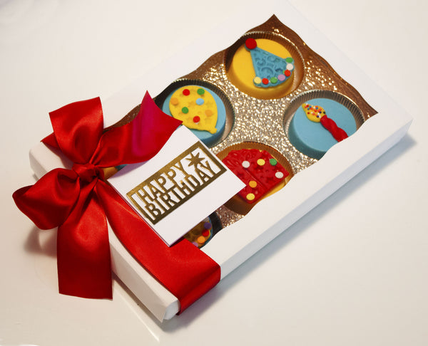 Image of a birthday gift in a white gift box with a red satin that contains candy coated birthday oreos® from Benedict Treats