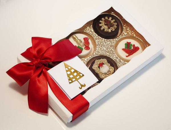 Image of a white gift box and red satin bow containing chocolate covered oreos® with a Santa's Workshop design as a Christmas cookie delivery gift from Benedict Treats