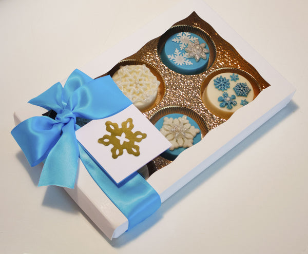 Image of nice white gift box with a blue satin bow containing chocolate covered oreos with a fun snowflake design as a holiday or christmas cookie delivery gift from Benedict Treats