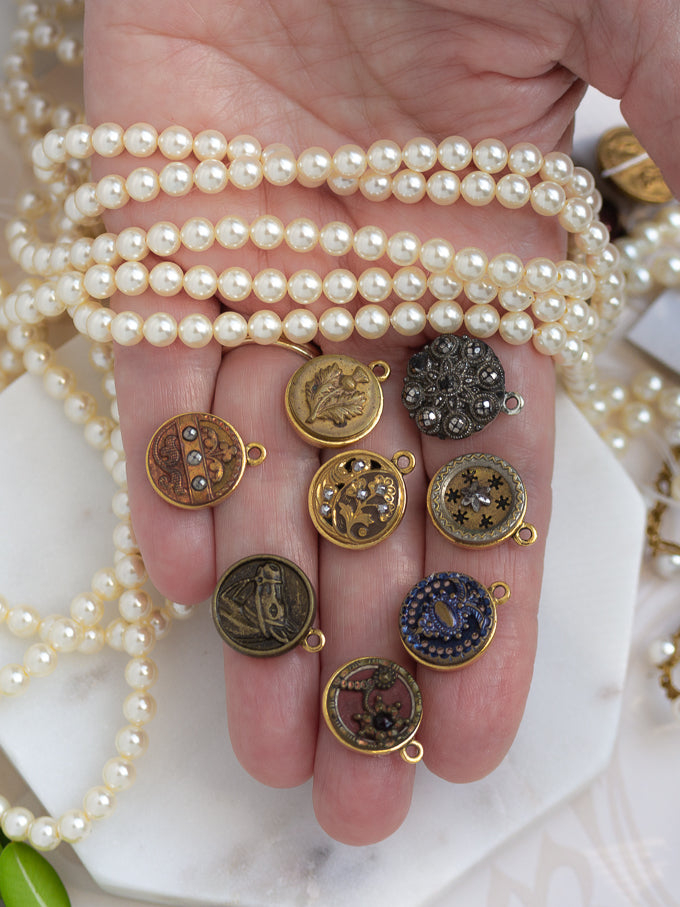 hand holding petite antique buttons and pearls