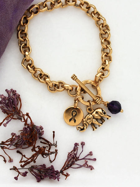 Alzheimer's bracelet with gold elephant, awareness ribbon, and purple crystal