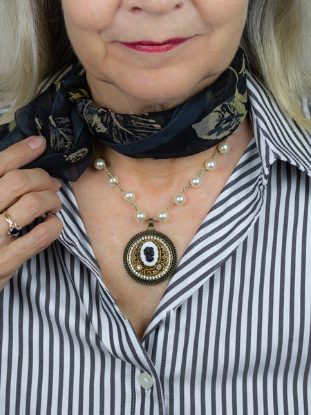 repurposed black and white cameo necklace worn with scarf and striped shirt