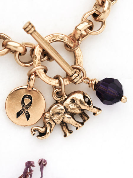 Alzheimer's bracelet closeup on elephant, awareness charm and purple crystal