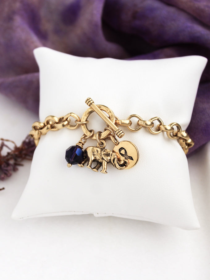 Gold alzheimer's bracelet with elephant, awareness ribbon, and purple Swarovski crystal