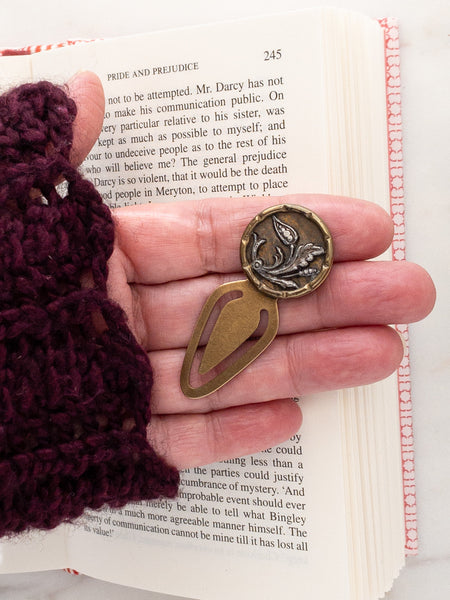 small bookmark with antique button in hand