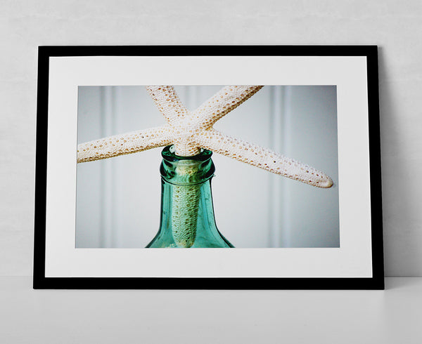 Infuse your home or space with a cool beachy feel. This photo print features a vintage sea glass bottle with a white glowing starfish.