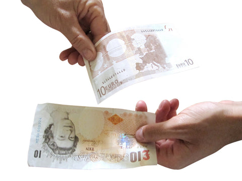 Two hands facing each other and each holding money as if to exchange it. One hand holding a Euro money and the other hand holding a pound money.