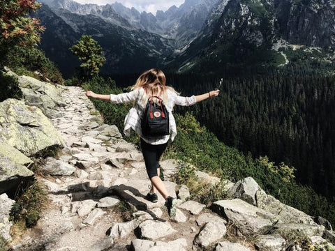 """5 Post Corona Virus Ways to """"Travel"""" Your Hometown - A girl hiking through a rocky trail with a black backpack on her back"""