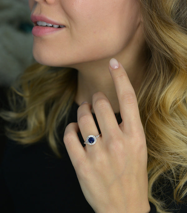 blue sapphire vintage engagement ring in a hand with model