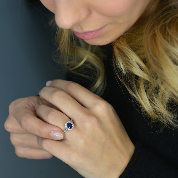 blue sapphire vintage engagement ring in white gold in a model's hand