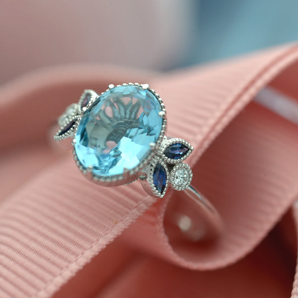 Oval oval blue aqua marine engagement ring with marquise sapphires white gold