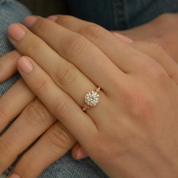 rose gold cushion halo engagement ring in a hand