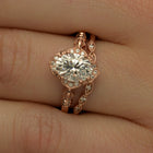 Oval Halo vintage look engagement ring with band shown in a hand